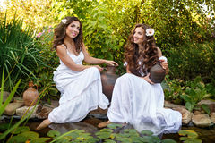Two sisters draw water from a pond. Stock Photography