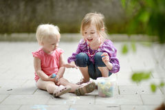 Two sisters drawing with chalk outdoors Royalty Free Stock Photos