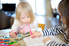 Two sisters drawing and learning together Royalty Free Stock Photo