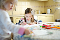 Two sisters drawing and learning together Royalty Free Stock Images