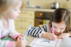 Two sisters drawing and learning together Stock Photography