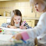 Two sisters drawing and learning together Stock Image