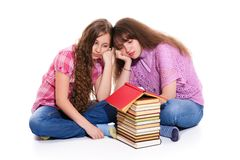 Sisters dream of their big house. The girls built a house of books. Isolation on a white background royalty free stock photo