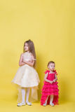 Two sisters in dresses on a yellow background look in different directions and offended Royalty Free Stock Image