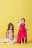 Two sisters in dresses on a yellow background and a mobile smartphone Royalty Free Stock Photo