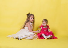 Two sisters in dresses on a yellow background photographed themselves on the phone Royalty Free Stock Image