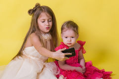 Two sisters in dresses on a yellow background photographed themselves on the phone Stock Image