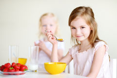 Two sisters eating cereal with milk Stock Photography