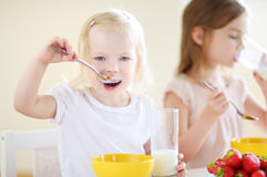 Two sisters eating cereal with milk Royalty Free Stock Photos