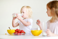 Two sisters eating cereal with milk Stock Images