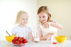 Two sisters eating cereal with milk Royalty Free Stock Image