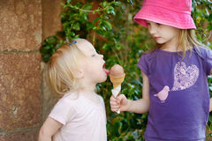 Two sisters eating ice cream outdoors Royalty Free Stock Photo