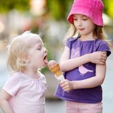 Two sisters eating ice cream outdoors. Two little sisters eating ice cream outdoors Royalty Free Stock Photos