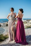 Two beautiful women, models, demonstrate evening dresses for events. Two sisters in elegant evening dress.  Girls with long healthy and shiny hair. Beautiful royalty free stock photo