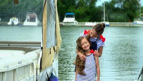 Two sisters embrace each other on a pier at water. Two sisters have fun at the yacht. On this video you can see as the little girl the blonde rotates around stock footage