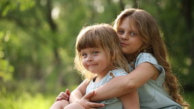 Two sisters embrace. Family time. Two sisters. The older girl hugging and kissing the younger. Family time stock video