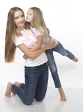 Two sisters embrace and kiss each other Stock Image