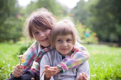 Two sisters embracing in summer. Two funny little sisters in summer park stock images
