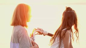 Two sisters enjoy weather on the beach. Two girls igat and talk among themselves stock footage