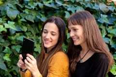 Two sisters enjoying of a day with a mobile Royalty Free Stock Image