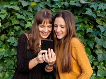 Two sisters enjoying of a day with a mobile Royalty Free Stock Photos