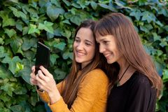 Two sisters enjoying of a day with a mobile Stock Image