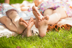 Two sisters feet lying on grass at park Royalty Free Stock Photos