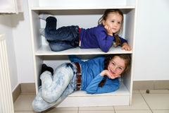 Two sisters fitting in storage rack Stock Photos