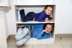 Two sisters fitting in storage rack Stock Images