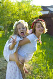 Two sisters frolic on the lawn in the summer Stock Images