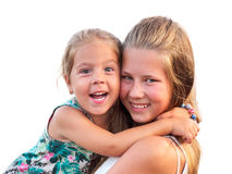 Two sisters fun hugging and looking into the camera. Royalty Free Stock Images