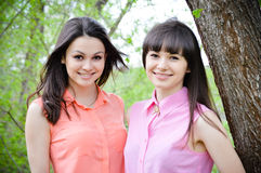 Two sisters girl friends smiling in spring. Two sisters or girl friends smiling, laughing and hug outdoors in spring or summer Stock Photography