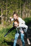 Two sisters girls friends teenagers riding each other having fun in the Park. royalty free stock images