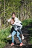 Two sisters girls friends teenagers riding each other having fun in the Park. stock photos