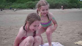 Two sisters girls play on the beach. Family holidays by the sea. Child playing with sand on the beach stock video footage