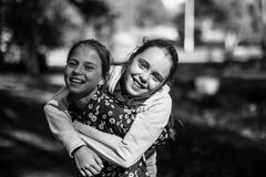 Two sisters girls teenagers having fun looking at the camera. Black and white photo stock photos