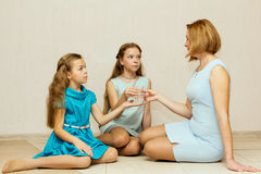 Two sisters give her mother a glass of water. Stock Photo
