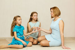 Two sisters give her mother a glass of water. Royalty Free Stock Photos