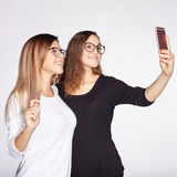Two sisters with glasses make selfie on phone royalty free stock photos