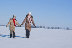 Two sisters go in the snow. Two sisters go in the deep snow Royalty Free Stock Photo