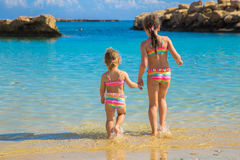 Two sisters go swimming in the sea. Stock Image