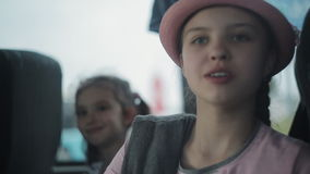 Two sisters go in a tourist bus, look out the windows and eat apples. Traveling in a tourist bus. Two little girls ride in a bus and look out the windows. The stock footage