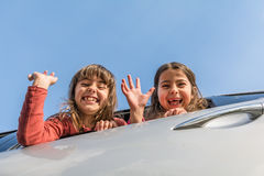 Two sisters going on the vacation and waving from inside the car Stock Photo