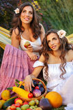 Two sisters and good harvest. Two cute sisters resting after harvesting close-up portrait. Ripe fruits and vegetables. Rich harvest . Agriculture Royalty Free Stock Photo