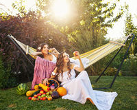 Two sisters harvest. Two cute sisters resting after harvest. Ripe fruits and vegetables Royalty Free Stock Photography