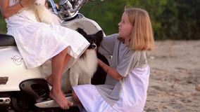 Two sisters have fun together. Two girls play with a dog near the moped at the sea. Two girls play and talk among. On this video you can see as the close-knit stock video footage