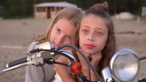 Two sisters have fun together. Two girls pose on the beach at the white moped. On this video you can see as the close-knit family has a rest on the seashore stock video footage