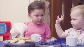 Two sisters having breakfast at the table. The elder taking care of the younger and wiping her hands and face with a napkin stock video footage