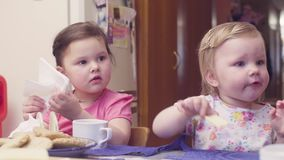 Two sisters having breakfast at the table. The younger is eating cheese, and the older is putting the napkins into a napkin holder stock video footage