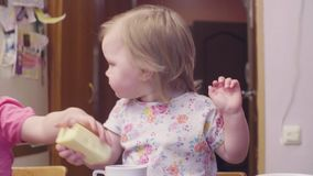 Two sisters having breakfast at the table. The younger taking a large piece of cheese and eating it. She looks very funny stock video